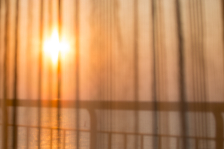 see through: blurred of room curtain see through the sea background in sunrise on vacation