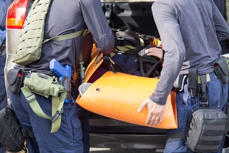 sufferer: law enforcement team use light stretcher for medical evacuation to vehicle in training course
