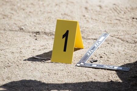 evidence marker and ruler scale of evidence  with law enforcement hand background Stock Photo