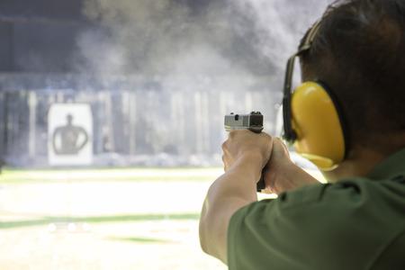aplicación de la ley apuntando y disparando pistola en el campo de tiro de la academia rodean con humo y copian espacio