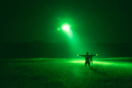 night vision: marshaller signal to helicopter pilot for night landing in medical evacuation training from night vision goggles view