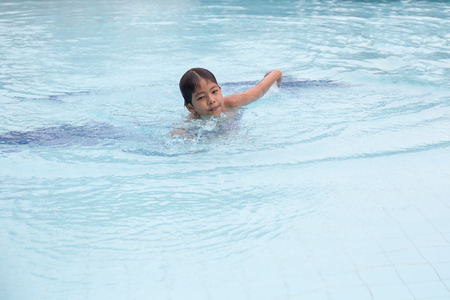 8 years old healthy Asian kid swimming training lonely in clean swimming pool at sport club with copy space