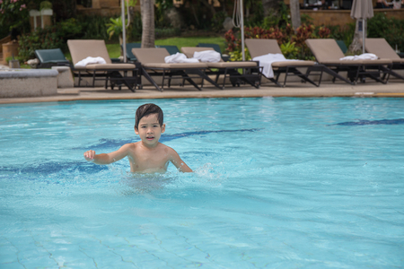 4 years old healthy Asian kid swimming lonely in clean swimming pool at sport club with copy space