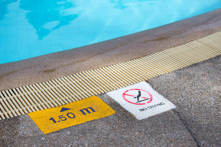 sign: no diving and depth sign warning at swimming pool edge with copy space Stock Photo