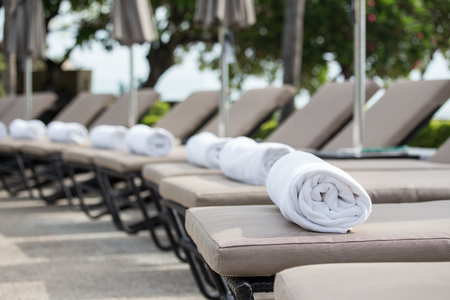 white towel roll on sunbeds at swimming pool with copy space Stock Photo