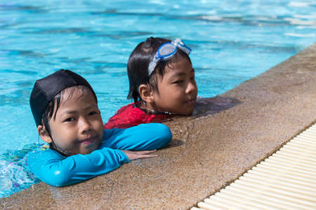 7, 8 years old healthy Asian brother and sister swimming together in clean swimming pool at sport club in summer with copy space