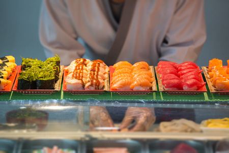 japanese sashimi and nigiri on sushi bar with blurred chef background Imagens