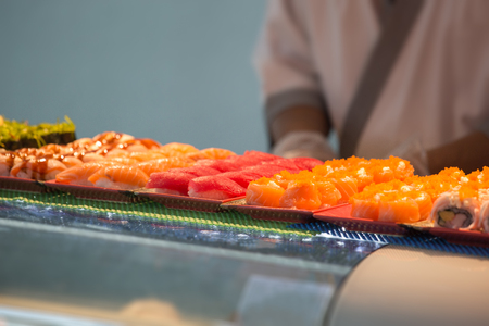 japanese sashimi and nigiri on tray with blurred chef background