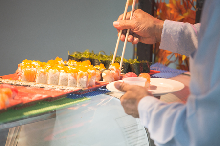 japanese sashimi and nigiri buffet on tray with customer chopsticks with  soft tone and copy space
