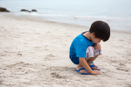 4 years old Asian boy sand writing lonely on beach at Hua Hin, Thailand with sea  background and copy space