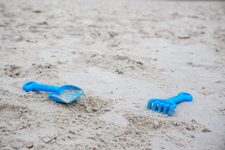 blue plastic sand construction toy for kid isolated on sand beach Imagens