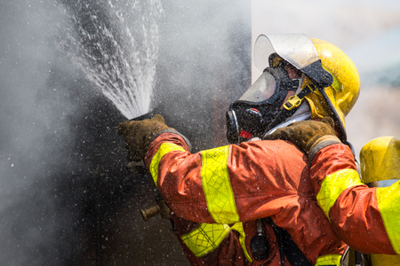 firefighter water spray by high pressure fire hose in smoke and droplets with copy space Imagens