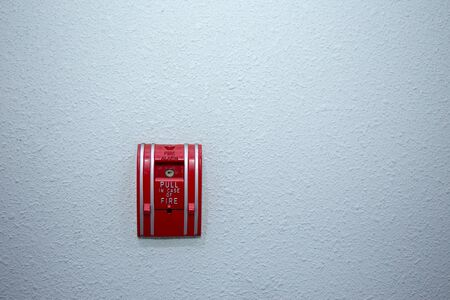 red fire alarm switch on blue wall background with copy space Imagens