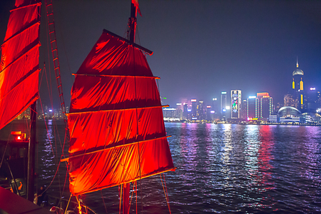 Hong Kong, China - December 9, 2017. Chineses red sail junk boat with landmark and Victoria harbour night scene with fog background in Hong Kong winterfest. Hong Kong  has one of the world's most festive Christmases Imagens - 92384015