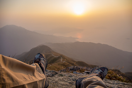 shoes and leg of hiker sit on peak with hiking trail and mountain range background with fog at sunrise in winter, Lantau Peak, Hong Kong