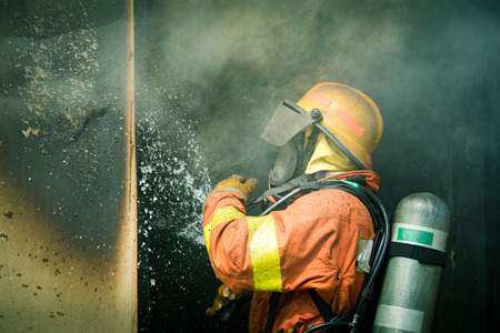 a firefighter water spray by high pressure nozzle to fire inside house surround by smoke with copy space in cenematic tone Imagens