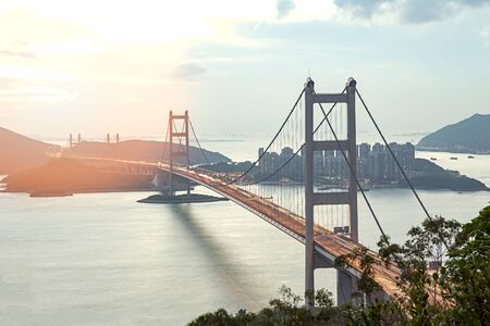 Silhouette Tsing Ma double-decked suspension bridge between Ma Wan island and Tsing Yi island in Hong Kong, China at sunset and flare