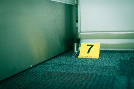 evidence marker number 7 on carpet floor with suspect object in crime scene investigation with copy space and cinematic tone