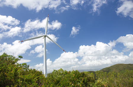 wind turbine system to produce green electricity for renewable energy at power station Lamma island, Hong Kong with mountain and blue sky background and copy space Imagens