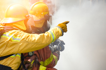 Close up action of two firefighters water spray by high pressure nozzle to fire surround by smoke with flare and copy space