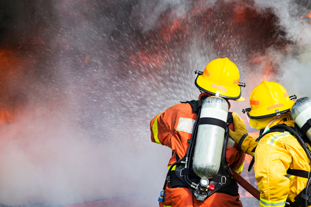 two firefighters water spray by high pressure nozzle to fire surround with smoke and copy space