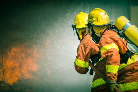 2 firefighters spraying in cinematic tone with copy space Imagens - 92501660