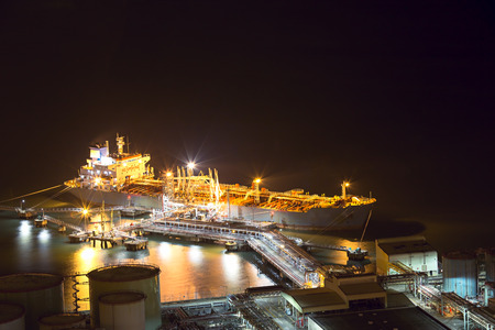 Night scene aerial view of big oil tanker ship loading at oil depot pier in power industry with copy space Imagens