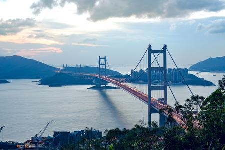 silhouette Tsing Ma double-decked suspension bridge between Ma Wan island and Tsing Yi island in Hong Kong, China at sunset Imagens - 92495673
