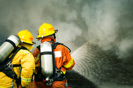 two firefighters water spray by high pressure nozzle to fire surround with smoke and copy space and cinematic tone Imagens
