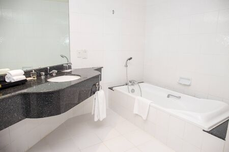 basin and bathtub with shower in white bathroom with copy space and nobody Imagens