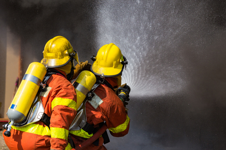 two firefighters water spray by high pressure nozzle surround with dark smoke and copy space