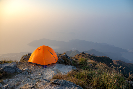 orange camping tent near cliff isolated on lantau peak, Hong Kong in sunrise and fog with copy space