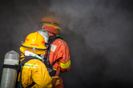 two firemen water spray by high pressure nozzle to fire and searching for rescue in dark smoke with copy space Imagens - 95387474