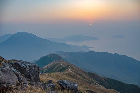 sea, mountain range and hiking trail view from lantau peak, Lantau island, Hong Kong at sunrise in winter season with copy space Imagens - 95366360