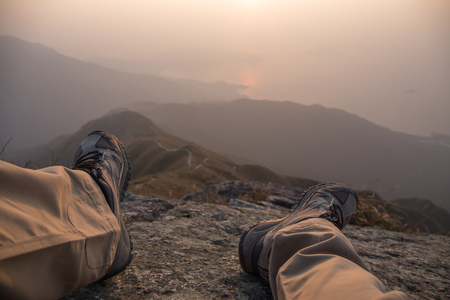 view of hiker pass his leg  sit on peak with hiking trail and mountain range background with fog at sunrise in winter, Lantau Peak, Hong Kong