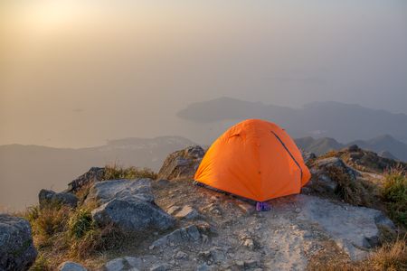 orange camping tent at cliff isolated on lantau peak, Hong Kong in sunrise and fog with copy space Imagens - 95393773