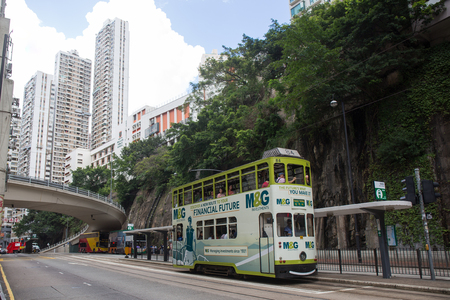 Hong Kong S.A.R. - July 13, 2017: Double decker tram or Ding Ding on the street in Causeway Bay Hong Kong.Tram or Ding Ding is major tourist attraction and one of the most environmentally friendly ways of travelling in Hong Kon Imagens - 98326833