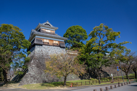 wooden turret or yagura on stone wall of Kumamoto castle in Japan and green tree with clear blue sky and copy space