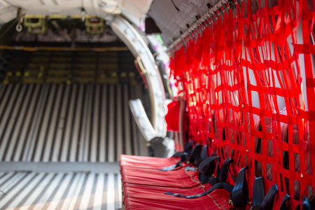 red net seat with seatbelt for paratrooper or airborn forces in military transport aircraft cabin CN 235 with copy space Imagens - 106381092