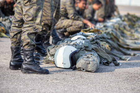 row of t-10 parachute with helmet and equipment standby on ground beside paratrooper in camouflage uniform and boots with copy space
