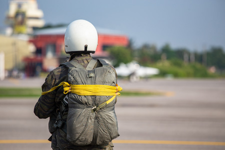 Police paratrooper in camouflage uniform and helmet with T-10 static line parachute  and equipment standby at airfield with copy space Imagens - 106381122