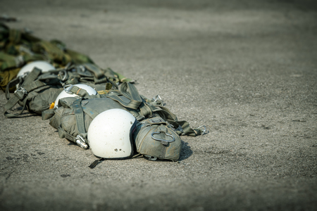 row of T-10 tactical parachute bag with parachute reserve and helmet on ground prepare for paratrooper to operation with copy space