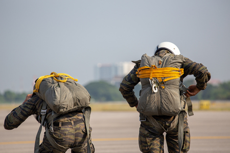Police paratrooper in camouflage uniform and helmet are checking T-10 static line parachute harness and equipment  for safety before tactical jump at airfield