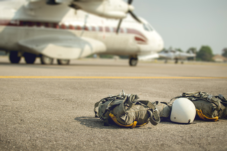 T-10 parachute with helmet and equipment for paratroop stanby on ground near military transport propeller aircraft for mission in cinematic tone with copy space 版權商用圖片
