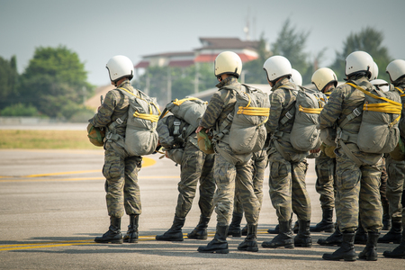 row of police special force paratrooper in camouflage uniform hold T-10 static line hook and parachute reserve in cinematic tone with copy space