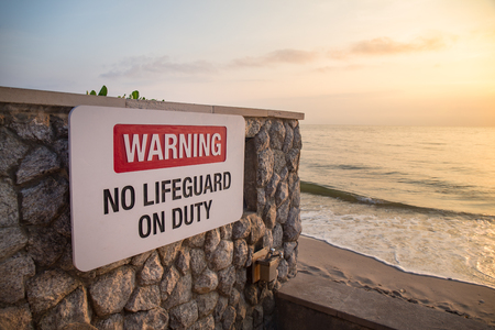 warning sign board 'no lifeguard on duty' on rock wall at beach with sea and sky background in sunrise and copy space Imagens - 106384539