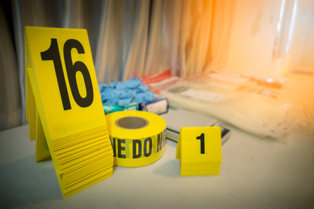 police line and evidence marker with forencsic science tool background on table for crime scene concept with copy space and flare Imagens - 106384548