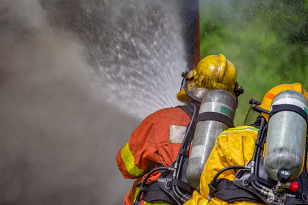 close up action of two firefighters water spray by high pressure nozzle to fire and  smoke with  copy space Imagens