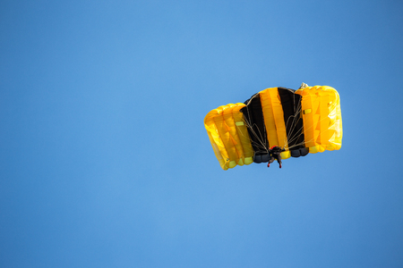 isolated skydiver in yellow parachute gliding after free fall jump with blue sky background and copy space