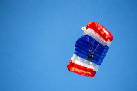 isolated skydiver in colorful parachute gliding after free fall jump with blue sky background  and copy space